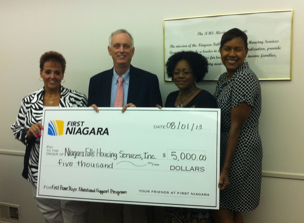First Niagara Buffalo Market Executive Buford Sears and Vice President Karla Gadley, right, present a $5,000 donation from the First Niagara Foundation to Niagara Falls Neighborhood Housing Services to fund educational support for first-time homebuyers. Accepting the donation on behalf of Neighborhood Housing Services is Kathleen Steinman, left, and Danielle Rice.