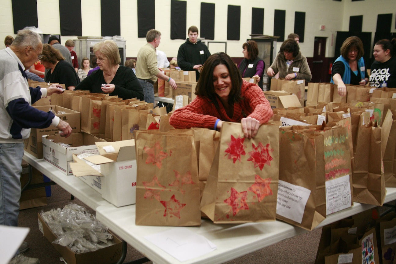 Volunteers help pack items to be donated.