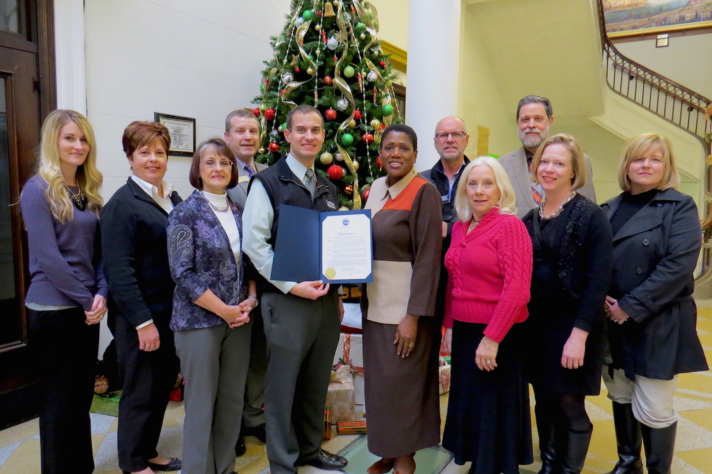 City of Niagara Falls Administrator Donna Owens, and Community Missions of Niagara Frontier Communications and Development Manager Christian Hoffman, both center, hold a proclamation wherein Dec. 1, 2015, was named #GivingTuesday in Niagara Falls. They are joined by representatives of Niagara University, the Isaiah 61 Project, Family & Children's Service of Niagara, the Niagara Falls Public Library and Opportunities Unlimited of Niagara.