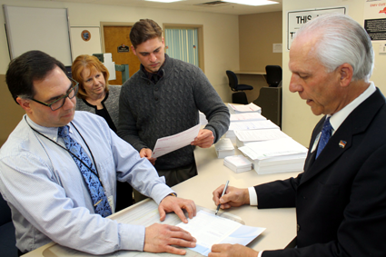 Assisted by Deputy County Clerk-DMV Jim Pulito, Niagara County Clerk Joseph A. Jastrzemski signs paperwork joining the New York State Donate Life Registry, the state's list of eligible organ donors. Reviewing Jastrzemski's paperwork are deputy clerks Matt Parish and Patti Weiss, who assisted at a donor registry sign-up event organized by Jastrzemski Tuesday in Lockport.