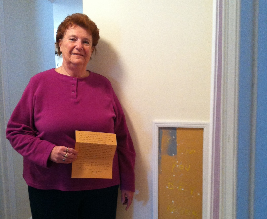 Beverly Weigel holds the `Love Letter` she submitted to the NTCC, and stands next to a message her late husband left her in the wall of their home.