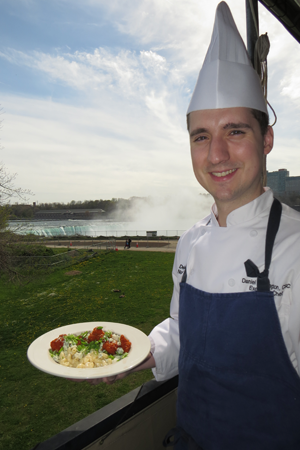 Top of the Falls Restaurant chef Daniel Thorington holds a plate of Buffalo mac and cheese.