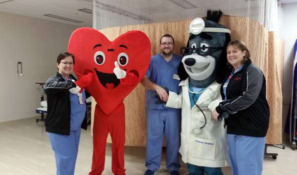 Members of the cardiac catheterization lab team at The Heart Center of Niagara get acquainted with some friends who will join them at Saturday's Healthy Heart Fair to showcase Memorial Medical Center's new Million Hearts Project. From left are Kelley Gombert, RNFA; the new Heart Center of Niagara mascot; Mitchell Aiken, CVRT; United Healthcare mascot Healthy Hound; and Tammy Skomski, RN.
