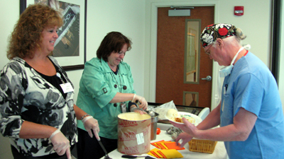 Clinical coordinators Janice Paternostro, R.N., left, and Janet Kundl, R.N., dish up cake and ice cream to Operating Room Technician D. Kim Reeves during a Nurses Day Reception held May 9 at The Heart Center of Niagara on the Niagara Falls Memorial Medical Center campus. At that event, officials announced the nursing staff will be honored at The Premier, Memorial's annual dinner and entertainment gala, for their dedication and commitment to delivering quality care.