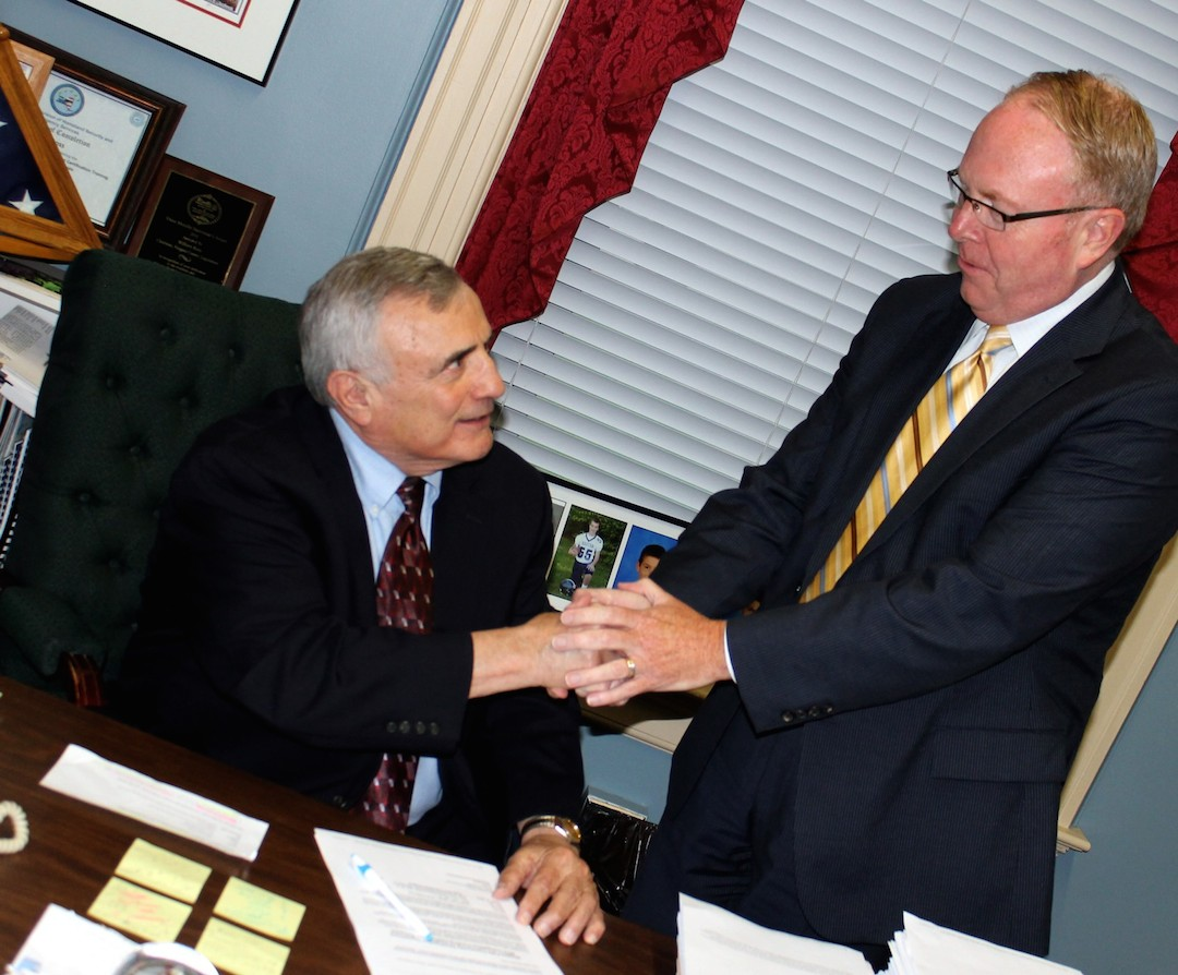 Niagara County Legislature Chairman William L. Ross, left, shakes hands with Niagara Tourism and Convention Corp. CEO John Percy Tuesday night after the two initialed the final draft of a contract between the county and the tourism promotion agency.