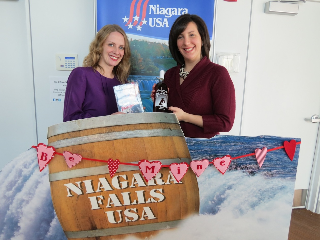 Love is in the mist in Niagara USA. Niagara Tourism & Convention Corp. Communications Manager/Interim Director of Marketing Michelle Blackley, left, and E-Marketing Coordinator Libby Woock showcase the components of a Valentine's Day prize that will be awarded to the writer of the best `Love Letter to Niagara USA,` a contest sponsored by the NTCC.