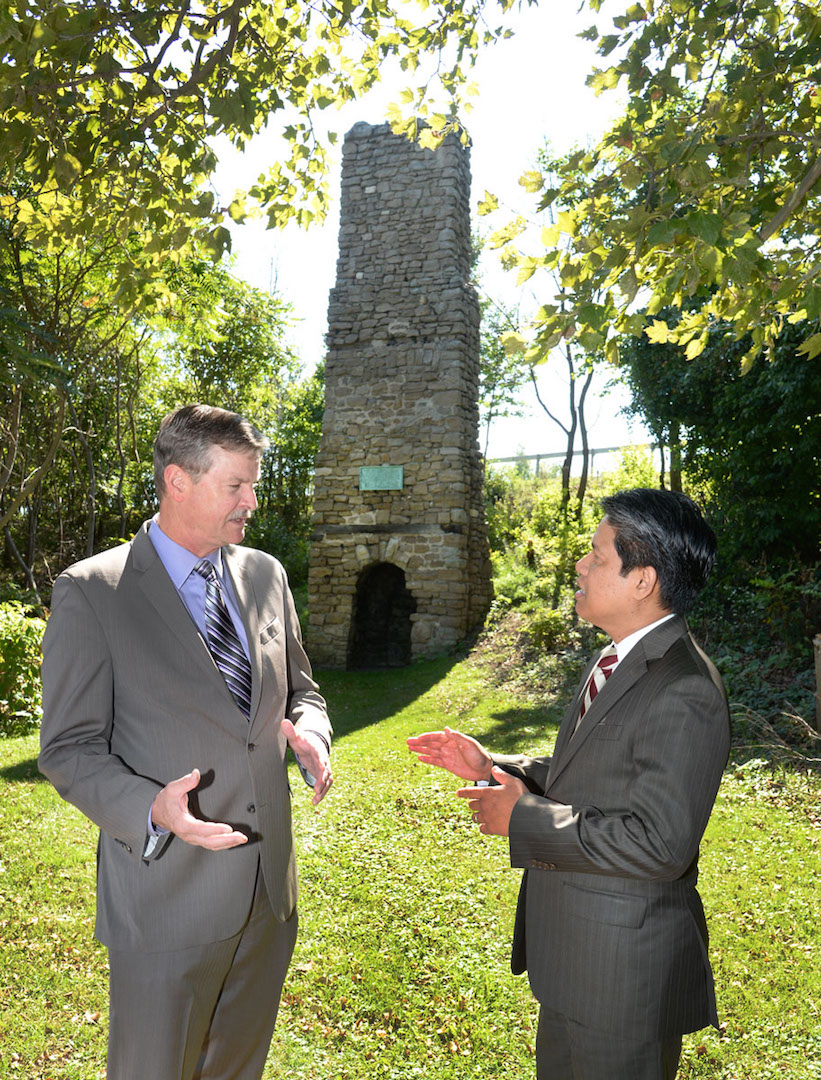 Mayor Paul Dyster, left, and Gil C. Quiniones, president and CEO of the New York Power Authority, stand in front of the Old Stone Chimney and discuss NYPA's plans to relocate the monument closer to the Niagara River to enhance public access. Located on NYPA property, the chimney dates back to the mid-18th century and was once part of French and British forts. (NYPA photo)