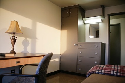 The standard room at Portage Road is furnished with a bed, desk and built-in wardrobe/dresser.