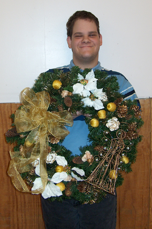 OUN's Niagara Flora Center and Greenhouse staffer Ken Kluge proudly displays an artificial wreath he helped make for sale to the public. Each wreath is unique.