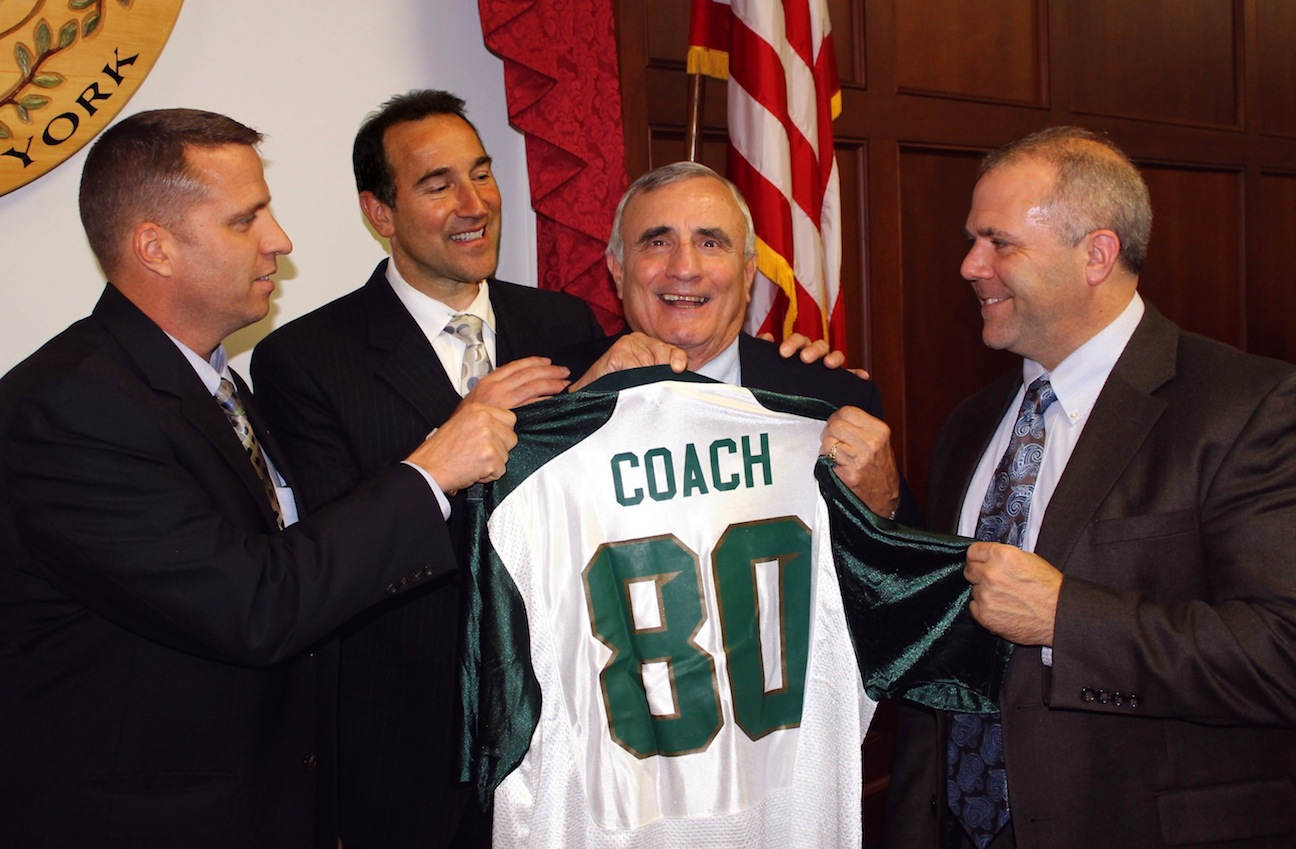 Niagara County Legislators Mike Hill of Middleport, Paul Wojtaszek of North Tonawanda and Majority Leader Rick Updegrove of Lockport flank Legislature Chairman William L. Ross during a departure from the Legislature's agenda to celebrate `The Coach's` 80th birthday. Hill, Wojtaszek and Updegrove presented Ross a Michigan State jersey.