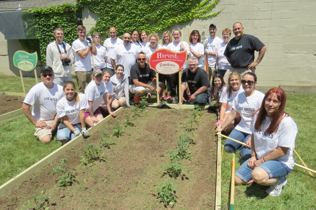 Pictured are the Wegmans volunteers with one of the community gardens they built Wednesday. Click for a larger image.
