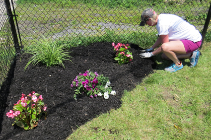 Amanda Tabaczynski works on a flowerbed at the Niagara Falls Boys & Girls Club.
