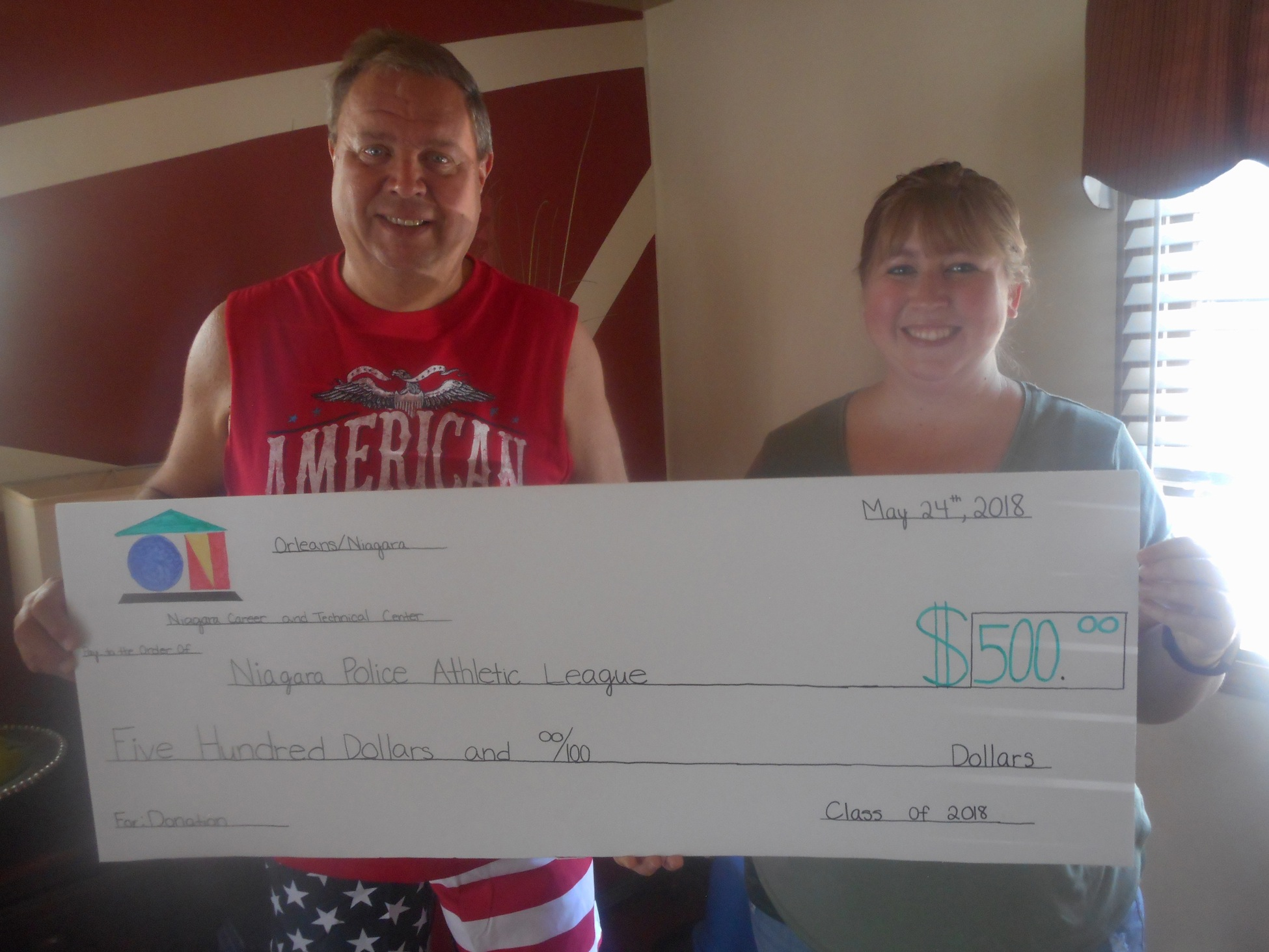 PAL President George Ihle and PAL volunteer Jennifer Florio are pictured together holding a $500 check.