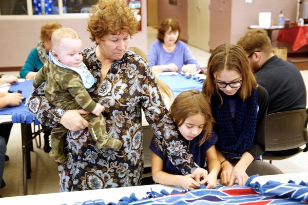 Community and church members work together to create no-sew fleece blankets for the Niagara Gospel Rescue Mission and the Magdalene Project during Barefoot Christian Community's `Serve Sunday.`