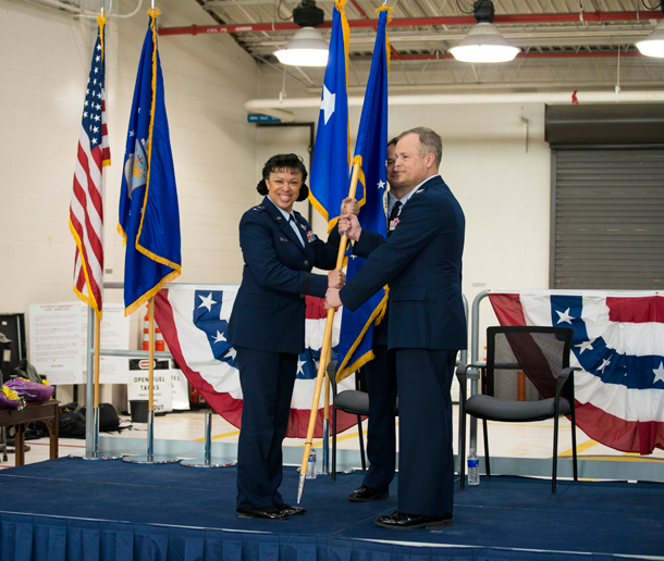 Maj. Gen. Stayce D. Harris, commander of the 22nd Air Force, Dobbins Air Reserve Station, Georgia, hands off the wing flag to Col. Brian S. Bowman as he assumes command of the 914th Airlift Wing, Niagara Falls Air Reserve Station. (U.S. Air Force photos by Tech. Sgt. Stephanie Sawyer)
