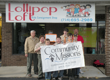 Members of Sanborn Boy Scout Troop 824 pose in front of Lollipop Loft Children's Consignment Store following their donation of more than 6,300 children's clothing items to Community Missions.