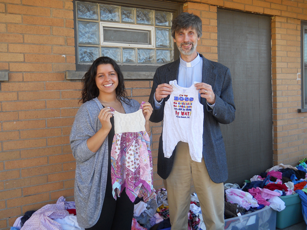 Kayla Kumm (left) of The CRIB Maternity Group Home joins the Rev. Mark Breese (right) of Community Missions as children's clothing items are displayed. Community Missions received a donation of more than 6,300 children's clothing items as part of a service project by Boy Scout Troop 824 of Sanborn.