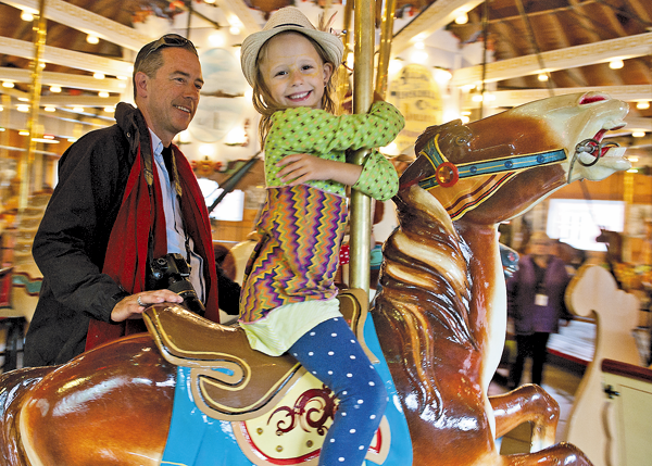 The Herschell Carrousel Factory Museum will celebrate the 100th anniversary of the Allan Herschell Co. this fall. The museum on Thompson Street in North Tonawanda is located in the complex of buildings where the company began. Shown, Roo Buckley stands with Ellah while she rides on the carousel Sunday at the Herschell Carrousel Factory museum. (Photos by Karen Gioia)