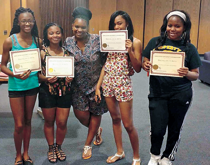 Shown is April Baskin, College Simulation Experience founder and executive director, center, as she stands alongside high school students who earned their fictional degrees after completing the challenges of the program.