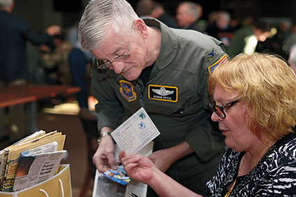 Col. (retired) Robin Pfeil, 914 Airlift Wing, former vice commander, and Edith Fose, general manager, base lodging, look through old postcards and photos.