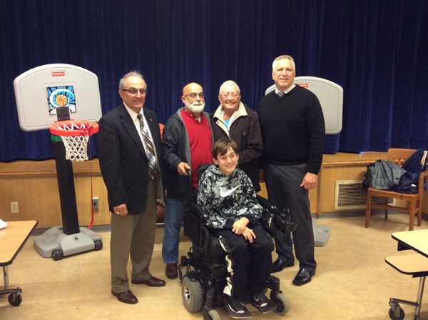 Kale Shiesley (center) poses for a photo with his grandparents and local officials at the new basketball court at Drake Elementary School named in his honor. Back row, from left, are, City of North Tonawanda Mayor Arthur G. Pappas, Kale's grandparents John and Terri Litten and Superintendent of Schools Greg Woytila.
