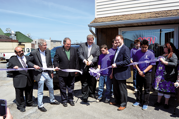 Empower CEO Jeff Paterson cuts the ribbon at the Empties for Empower grand opening ceremony. He is surrounded by officials and members of the organization. From left: Empower Board President Dr. Salvatore Passanese, Kevin Penberthy (Office for Persons with Developmental Disabilities Region 1 deputy director), state Assemblyman John Ceretto, Paterson, Santino Bax, state Sen. Robert G. Ortt, James Olan and worksite supervisor Jill Patterson. (Photo by Lauren Zaepfel)