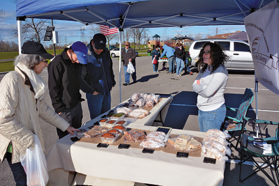 Visitors browse baked goods from Rise Up Breads & Bakery.