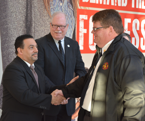 Town of Niagara Active Hose Co. Fire Chief Daniel J. Hosie shakes hands with Town of Niagara Deputy Supervisor Charles F. Teixeira after accepting a donation of behalf of the company's active group.