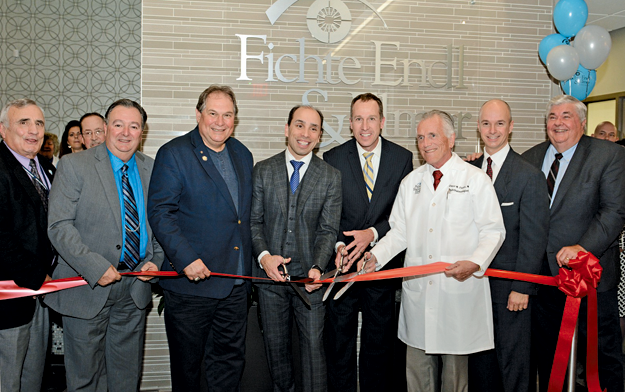 Doctors gathered with officials as they cut their ribbon to mark the grand opening of the new Fichte Endl & Elmer Eyecare location in the Town of Niagara. From left: Niagara County Legislator Bill Ross stands with Town of Niagara Supervisor Lee S. Wallace, Assemblyman John D. Ceretto, Drs. Michael J. Endl, Thomas R. Elmer Jr. and Claus M. Fichte, Calamar President and CEO Kenneth Franasiak, and Niagara County Clerk Wayne F. Jagow. (Photos by K&D Action Photo and Aerial Imaging)