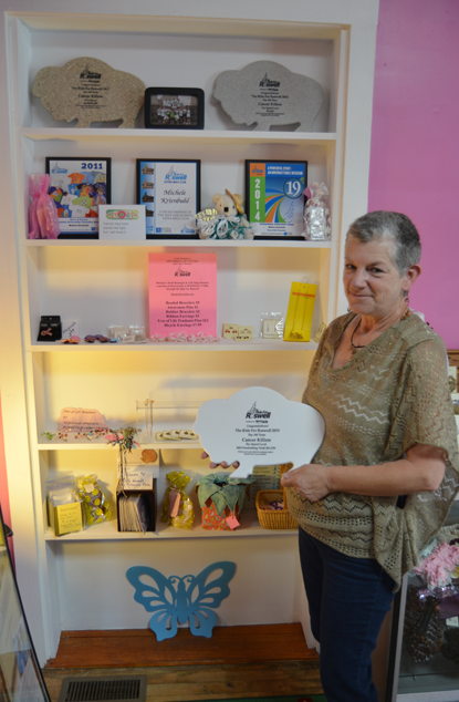 Michele Krienbuhl stands by shelves of merchandise at her business, Michele's Motif, where 100 percent of the sale is donated to the Roswell Park Cancer Institute.