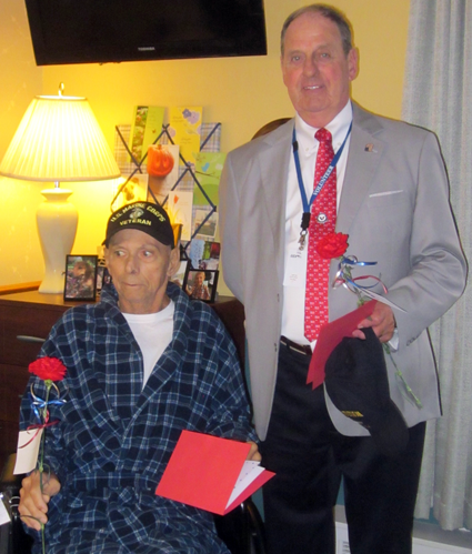 Hospice at Jeanne's House resident and U.S. Marine Corps veteran James Oliverio receives a Veteran's Day card and carnation from Niagara Hospice volunteer and U.S. Air Force veteran James Hildreth on Veterans Day.