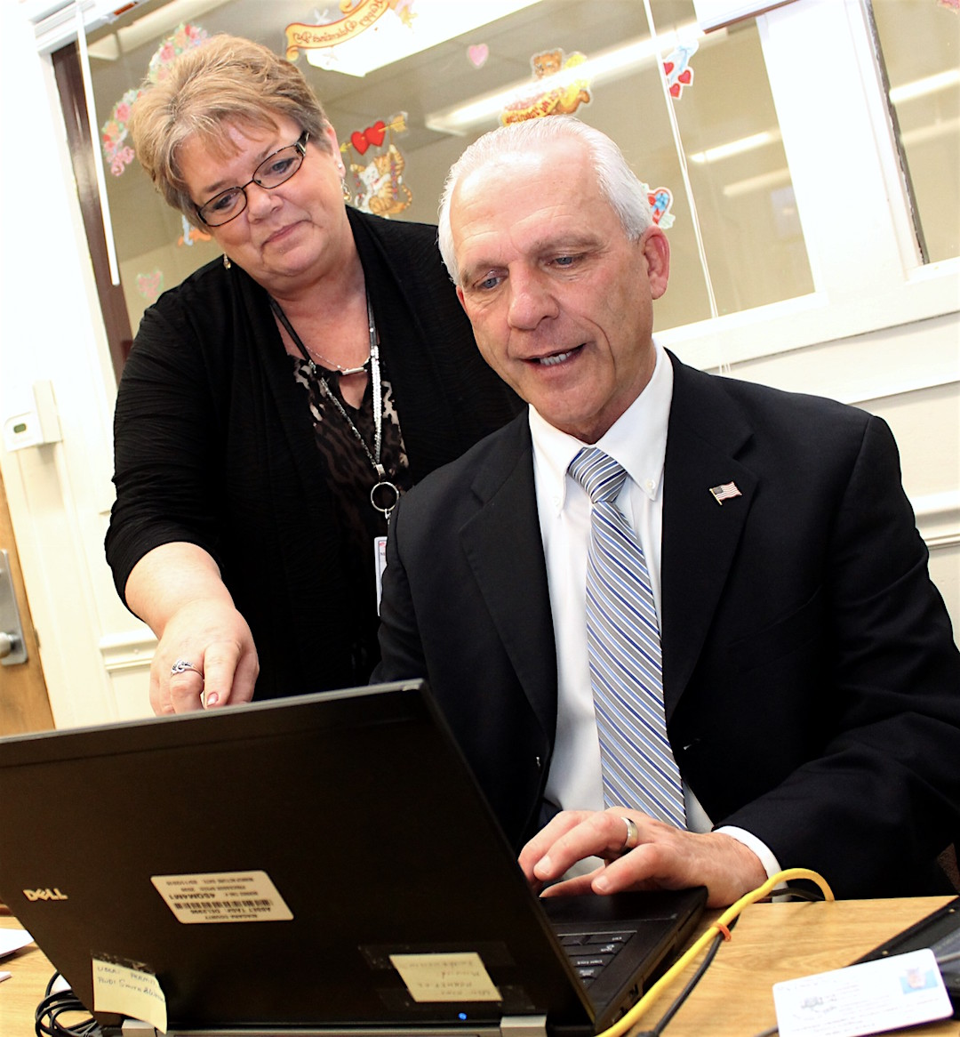 Niagara County Clerk Joe Jastrzemski uses a public computer terminal to log onto the New York State Police pistol permit recertification website while in the Niagara County pistol permit office. Pistol Permit Clerk Janice Rider looks on.