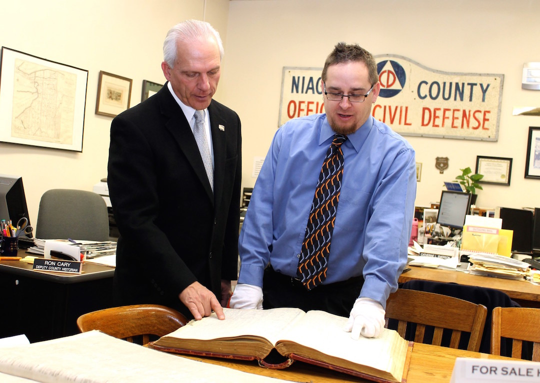 Niagara County Clerk Joseph Jastrzemski reviews a book containing his own grandparents' immigration records during a visit to the Niagara County Historian's Office. As county clerk, Jastrzemski oversees the historians' operation, and was visiting to revamp the office's work schedule to increase historians' availability to members of the public researching history and genealogy by an additional 153 hours per year.