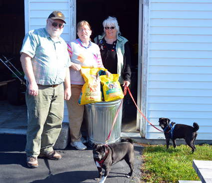 With help from Gordon Ross and Amy McQuay, Paulette Coty (right) displays a bin of donations made to Mario's Pet Food Pantry alongside her dogs, Antonio and Flavio.