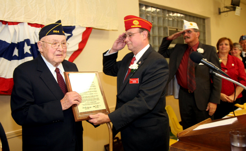 American Legion National Commander Daniel Dellinger salutes 100-year-old World War II veteran Elmer Moje of Wheatfield during an official visit to Western New York. Dellinger and Department of New York Commander Kenneth Governor presented Moje with the Department Commander's Award of Excellence during a dinner at Sikora Post 1322 in North Tonawanda. At right are Department Adjutant Jim Casey and Department Auxiliary President Barbara Corker. (photo by Doug Malin)