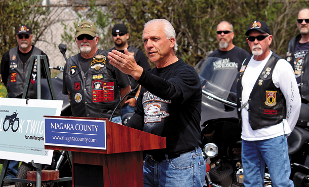 As representatives of area motorcycle clubs look on, Niagara County Clerk Joseph Jastrzemski rolls out his motorcycle safety awareness initiative, urging motorists to live by the mantra `Look Twice, Share the Road.` (Photo by Christian W. Peck)