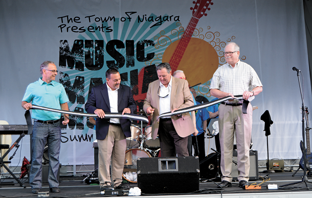 Town of Niagara Supervisor Lee S. Wallace, with the help of some of the town's board members, cuts the ribbon revealing the town's new concert stage. From left: Councilman Samuel S. Gatto, Deputy Supervisor Charles F. Teixeira, Wallace and Councilman Marc M. Carpenter.