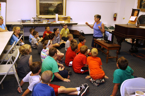 History Center of Niagara volunteer Jean Weisbeck explains an activity to children at last year's summer program.