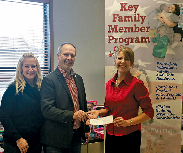From left: NCBA Board of Directors and Show Chairwoman Kristin L. Savard, PE, of Advanced Design Group and NCBA President Gary Pollard of Pollard Windows and Doors present a check to Holly Curcione of Friends and Family Support Association.