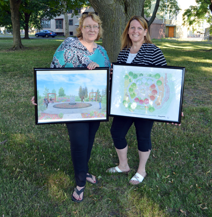 Co-chairs of the children's memorial project MaryBeth Kupiec (left) and Paula Benedyczak hold up two renderings of the garden. Landscape architect Frank Brzezinski designed the memorial.