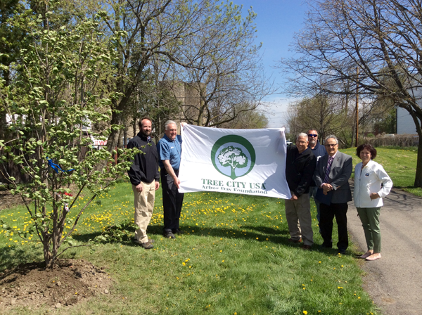 Officials hold up a Tree City USA Arbor Day Foundation banner. Pictured, from left, are Patrick Marren, senior forester with the New York State Department of Environmental Conservation; Brad Rowles, Department of Public Works superintendent; Robert Pecoraro, alderman-at-large; Craig Anthony, park maintenance crew leader, Arthur G. Pappas, mayor; and Patty Brosius, parks and recreation director.