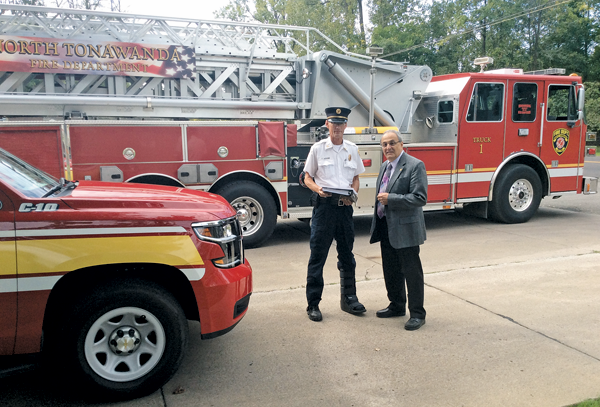North Tonawanda Fire Chief John Lapham (left) and Mayor Arthur G. Pappas, review the specifications of the new fire pumper.