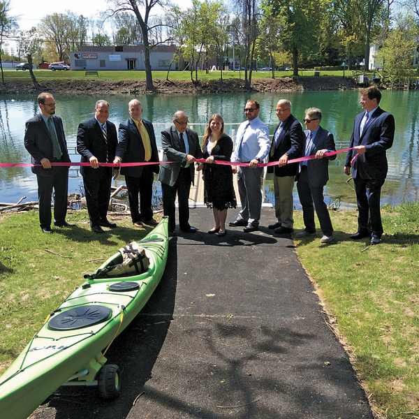 City officials surround North Tonawanda Mayor Arthur G. Pappas (center) as he cuts the ribbon for the city's new bike extension and kayak launches.
