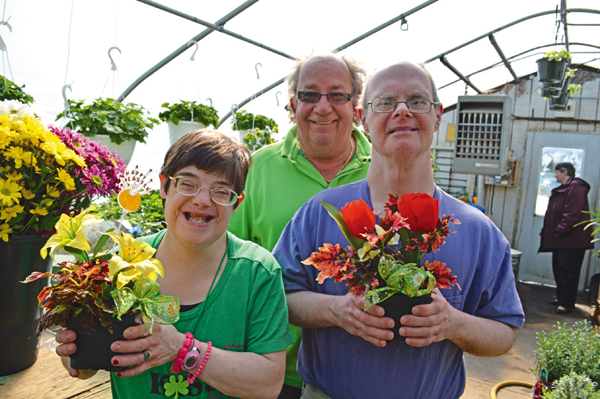 Horticulture therapy program participants Connie Greer and Ricky Koban hold arrangements they made with the help of greenhouse coordinator Bob Bracikowski.
