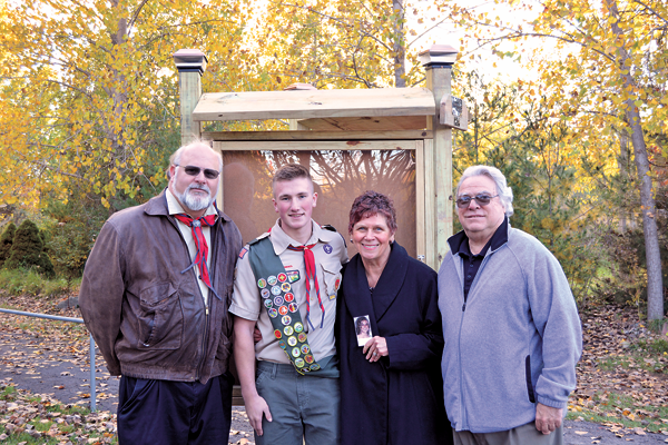 From left, Troop No. 841 Scout Master Kevin Rolling stands in front of the newly constructed information board at the Kimberly Woodruff Memorial Nature Trail with Scout Thomas Berner and Barbara and Jim Woodruff. Barbara is holding a photo of her daughter, Kimberly, whom the trail is named after.