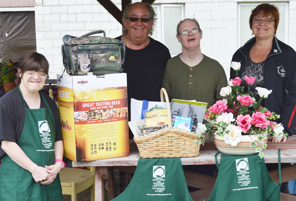 Connie, Bob, Ricky and Ona display a variety of the items to be auctioned at the upcoming Vines & Wines on May 21. Ona Sherman is the co-chair of the event. Bob Bracikowski is the greenhouse coordinator at Opportunities Unlimited of Niagara. Connie Greer and Ricky Koban participate in the horticulture programming at the agency's Wheatfield day program location.