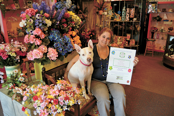 Amy Sileo, owner of Sherwood Florist, who leads the Oliver Street Merchants Association, sits with her dog, Luna, at her business where the next cash mob will be held at 5 p.m. Wednesday, June 22. Sileo is holding a sign she will place in her window promoting the event.