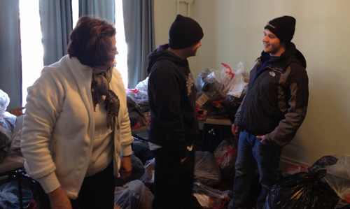 Shown are Jennifer Cooper, John Cooper Jr. and Eddie Gauthier organizing coats, hats and gloves for distribution.