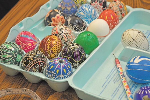A crate of pysanky in different states of completion.