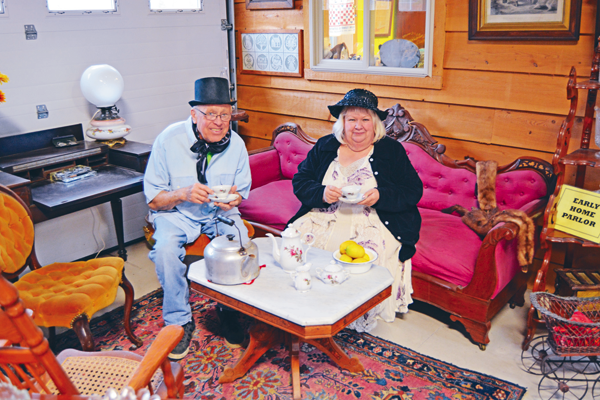 Sanborn-Lewiston Farm Museum Curator Bonnie Haskell and Glenn Wienke, museum treasurer and program and publicity chairman, raise their teacups while sitting amongst the museum's Victorian living room display.